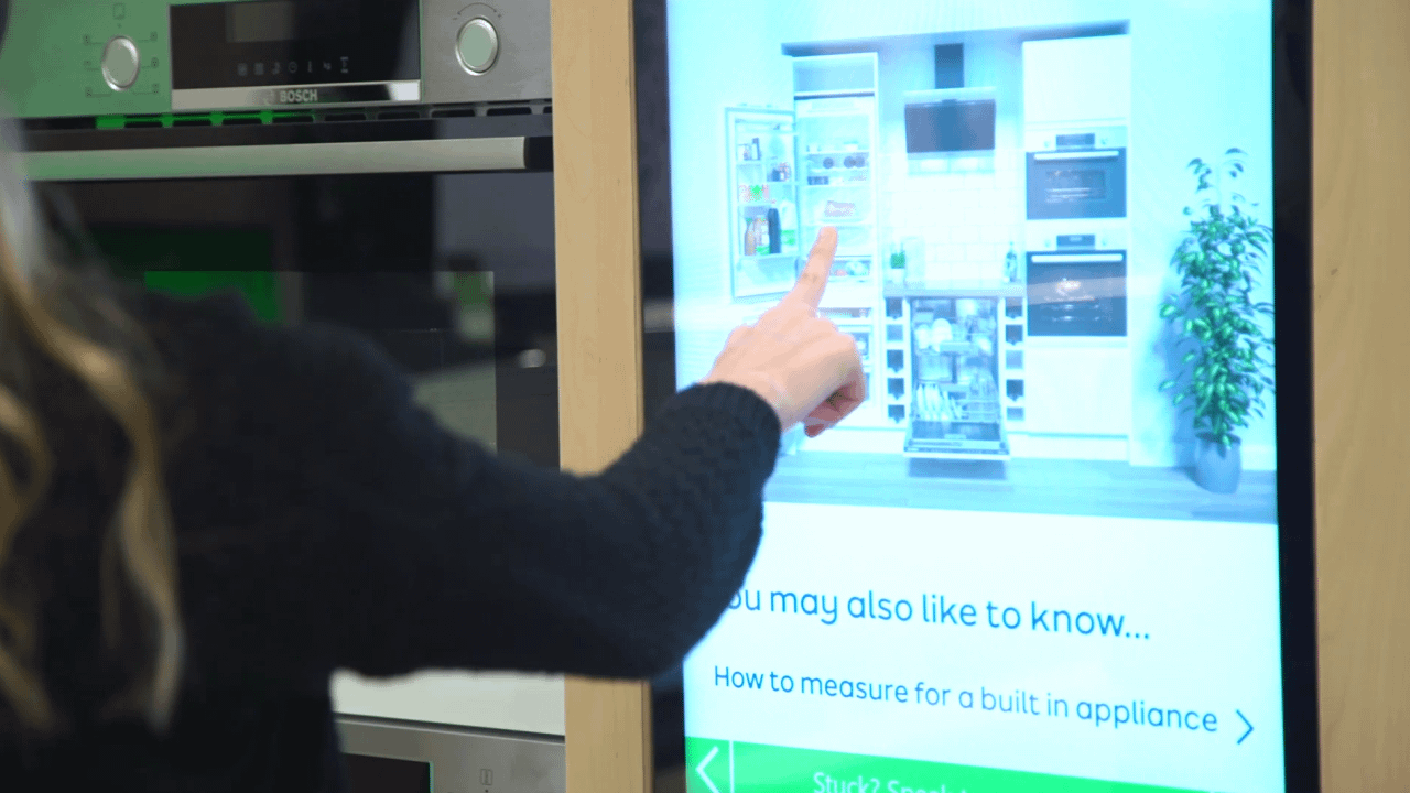Customer using touch screen digital signage in an electrical retail store to learn about built-in applicances