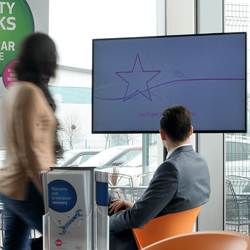 Man and woman looking at digital signage screen in a car showroom