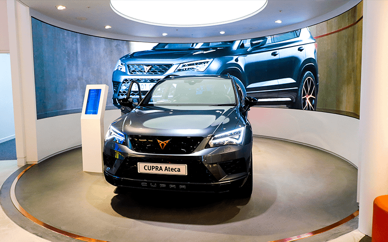 Cupra Ateca in front of a curved video wall in a car showroom