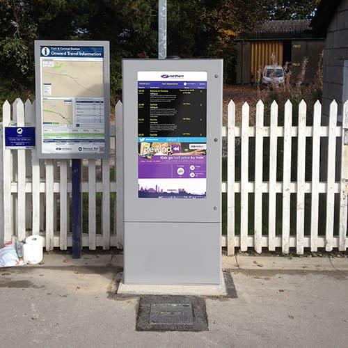 Outdoor digital signage totem showing passenger information at a train station