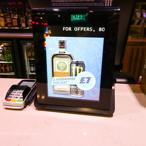 Digital signage in a bar showing drinks promotions