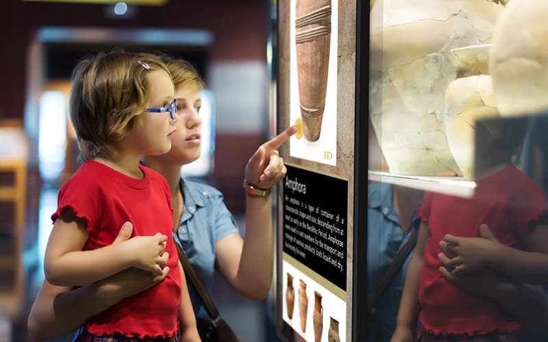 Woman and child using NEC touchscreen digital signage at a museum