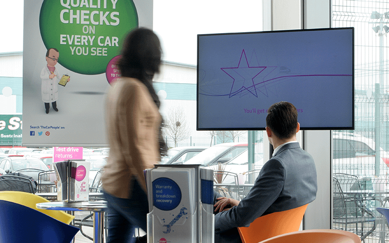 Man and a woman looking at digital signage in a car showroom