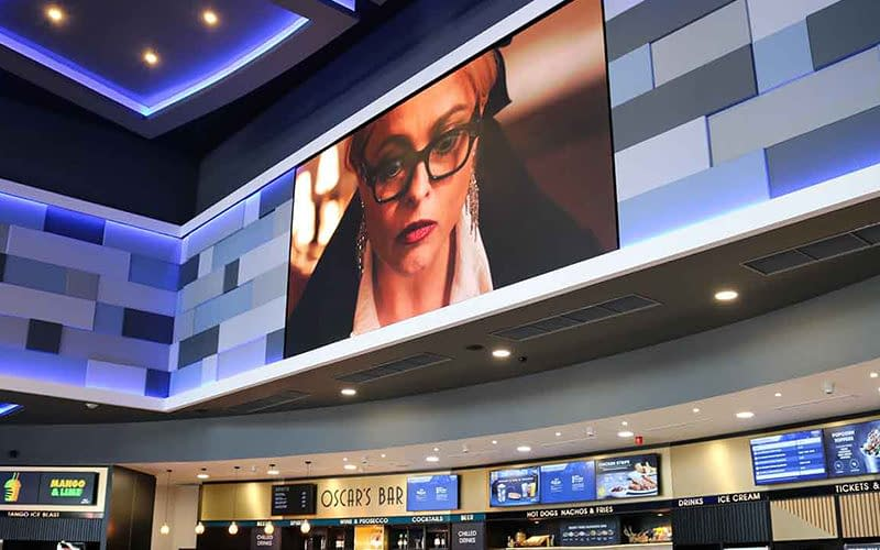 Large format digital signage screen in a cinema showing trailers