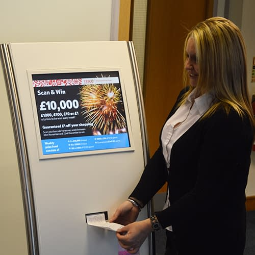 Woman using freestanding ticket kiosk