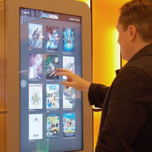 Man using touchscreen digital signage at a UK cinema