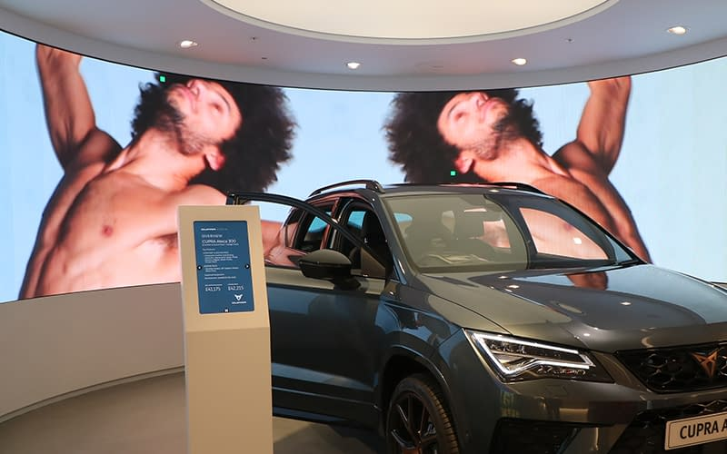 Grey Cupra in front of a curved video wall in a car showroom