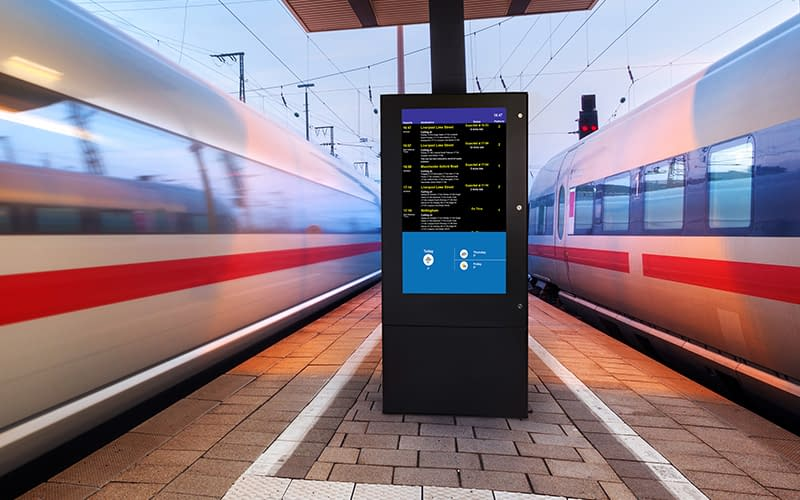 Digital signage display showing timetable information to passengers at a UK train station