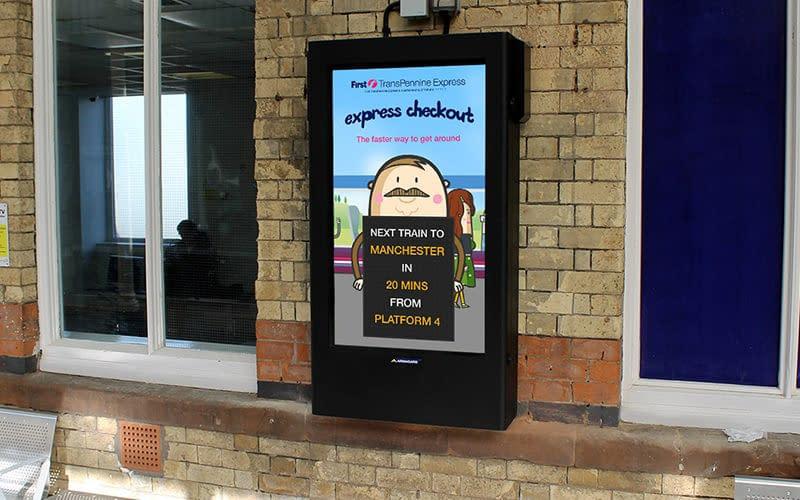 Wall-mounted digital signage on a railway platform showing train proximity