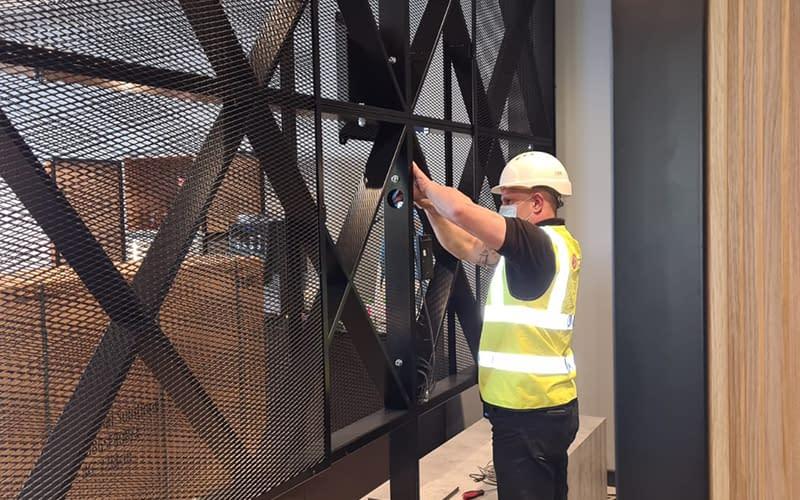 Man in PPE installing digital signage