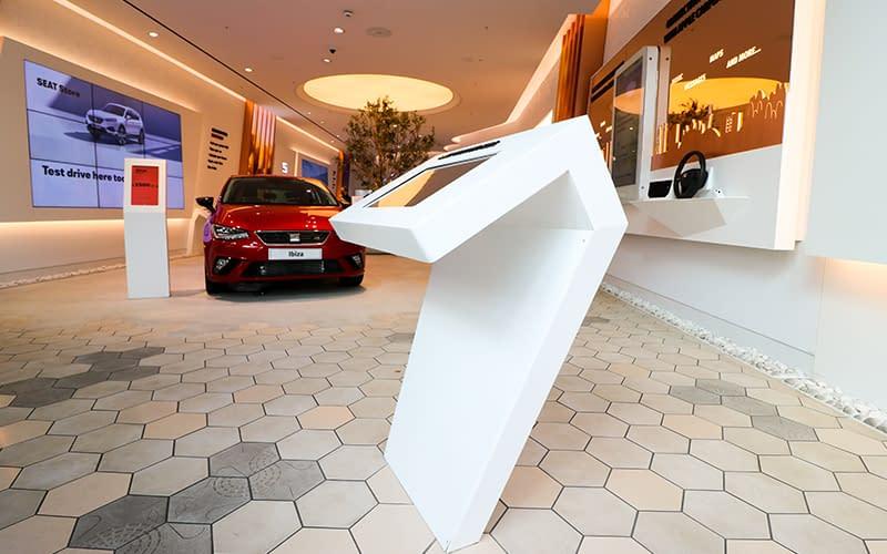 Bespoke white freestanding futuristic digital signage enclosure in a SEAT car showroom