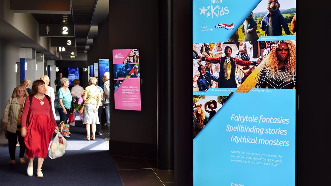People in corridor in a cinema looking at digital signage