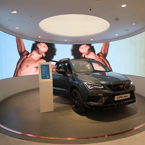Cupra Ateca vehicle parked in front of a curved video wall in a car showroom
