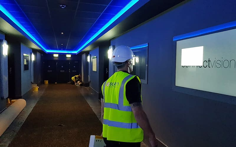 Engineer in PPE carrying digital signage equipment