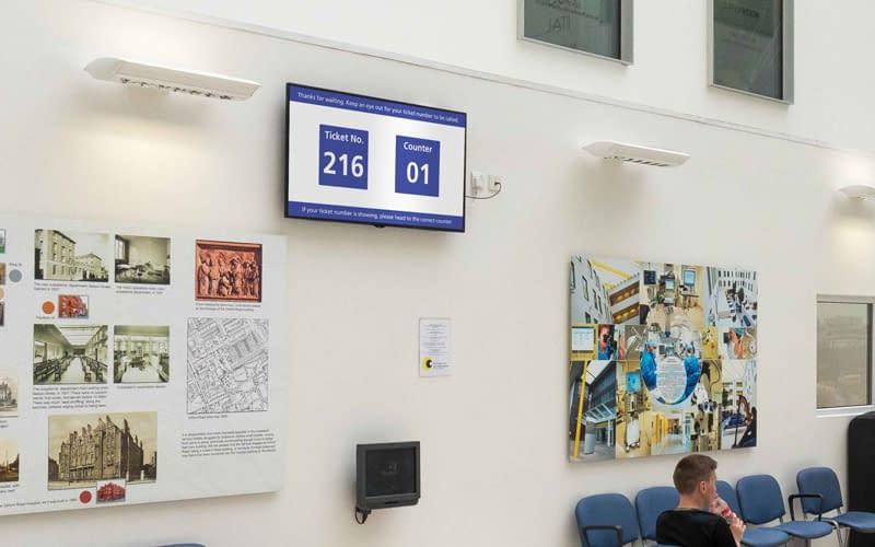 Digital signage in a waiting room managing queues